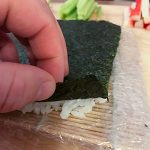 Nori sheet with flattened rice below