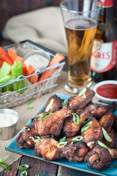 Jerk chicken wings on a plate with beer and veggies