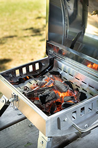 portable bbq on a park table with hot charcoal