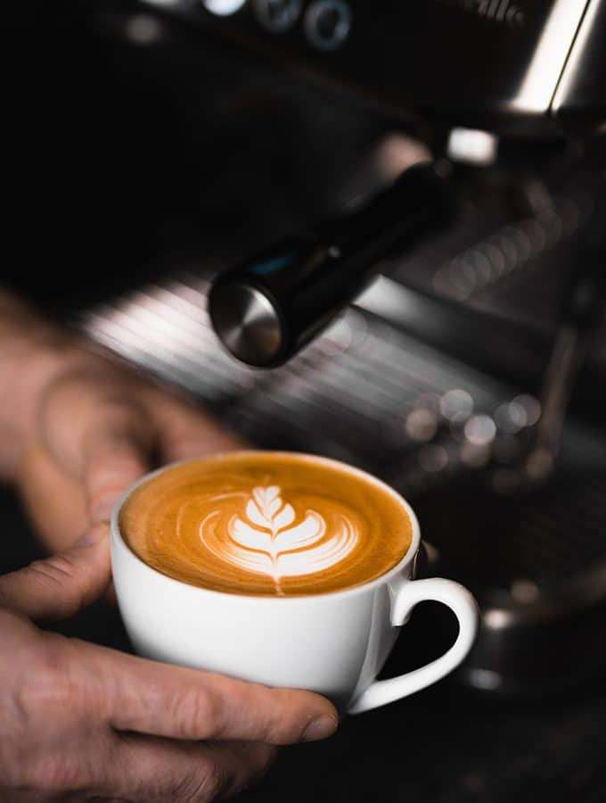 latte art in front of an espresso maker