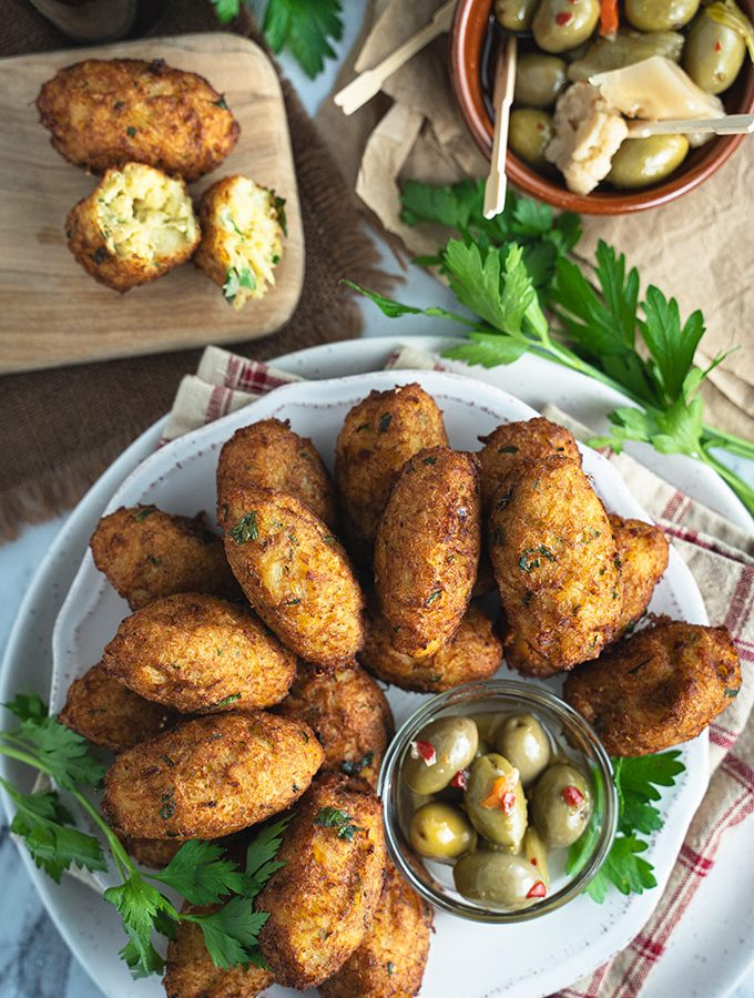 Cod fritters on a plate with green olives