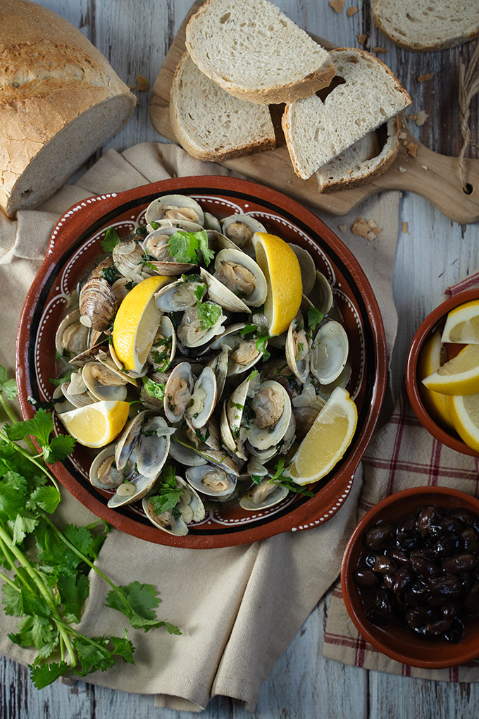 Portuguese garlic and wine clams - Amêijoas à Bulhão Pato on a red  clay plate.