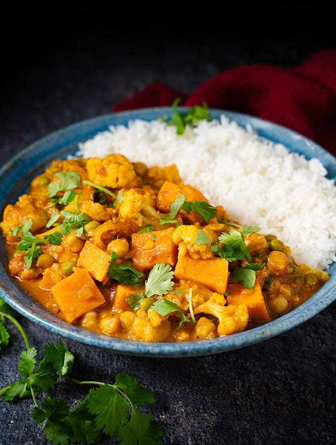 Vegetable curry with rice in a blue bowl
