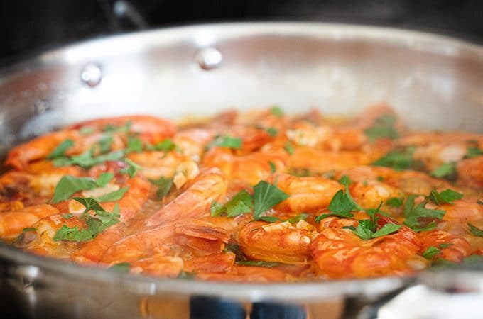 Shrimp in a frying pan on the stovetop over a flame