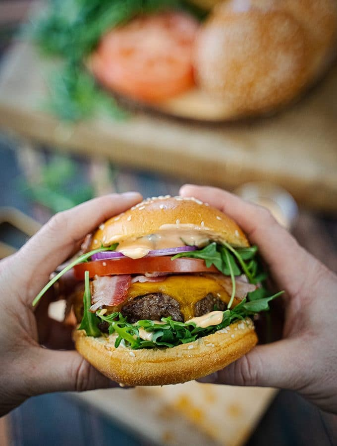 Closeup of a large and load burger being held in two hands