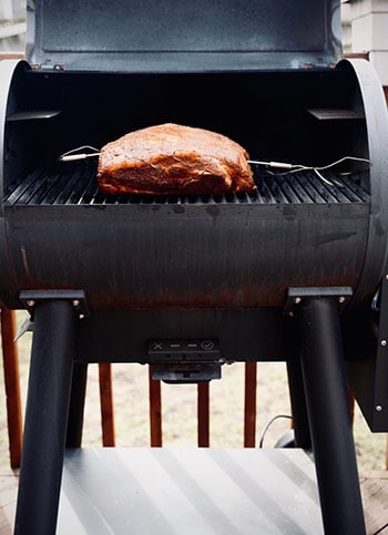 Pork butt inside a smoker on the cooking grates, with temperature gages stuck in the meat.