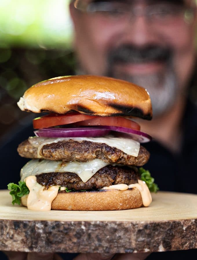 Me out of focus holding up a double burger on a wood platter