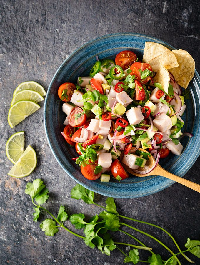 Ceviche in a blue bowl, beside lime wedges and cilantro