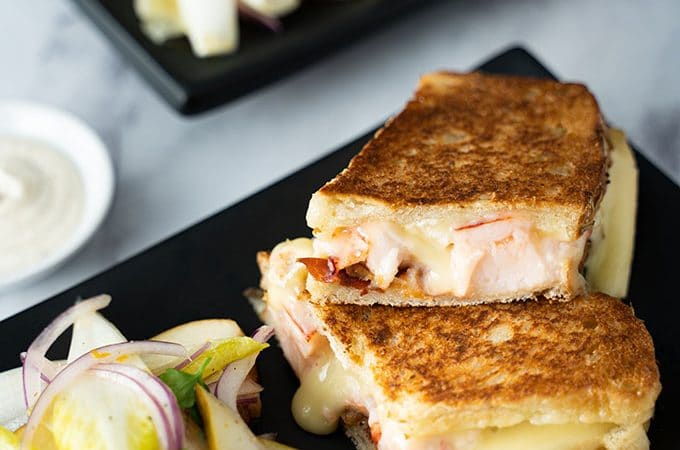 Two lobster grilled cheese sandwiches with salads on black plates